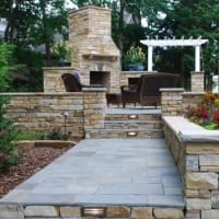 Paver walkway with wall and patio with fireplace